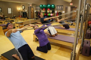Thigh Stretch in a Pilates Tower class.